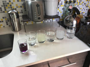 Cups with different liquids before the experiment - they are all colorless (or light yellow)